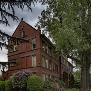 Eaton Hall at Willamette University campus behind the trees and flowers.