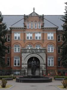 Statue and fountain in front of Gonzaga University brick building.