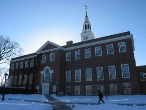 Student walking in the snow in front a building at Dartmouth College.