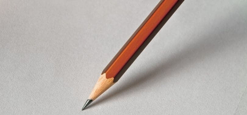 A brown pencil against a white piece of paper.