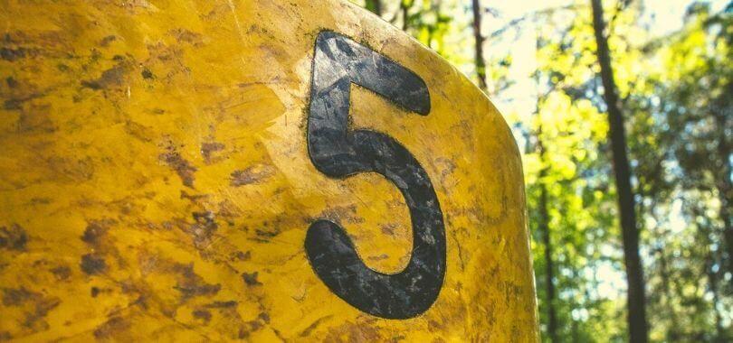 A five printed on a brown metal siding.