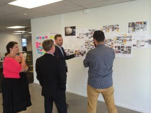A man is pointing his hand on the whiteboard with images on it while discussing to three people.
