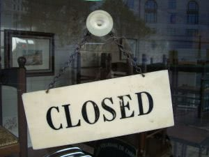 """""""Closed"""" signage behind a glass wall."""