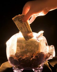 Hand dropping a dollar bill in a transparent piggy bank.