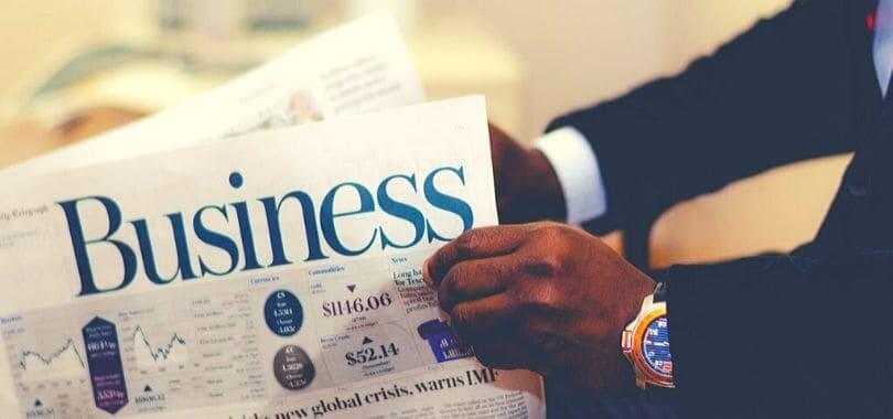 """A person holding a newspaper with """"business"""" printed on it."""