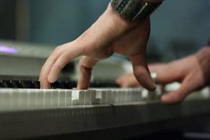 A hand is paying the piano shown below.