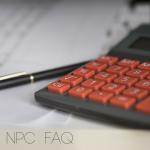 A black calculator with orange buttons showed in half. Black pen beside it.
