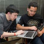 Two male students looking at the laptop.