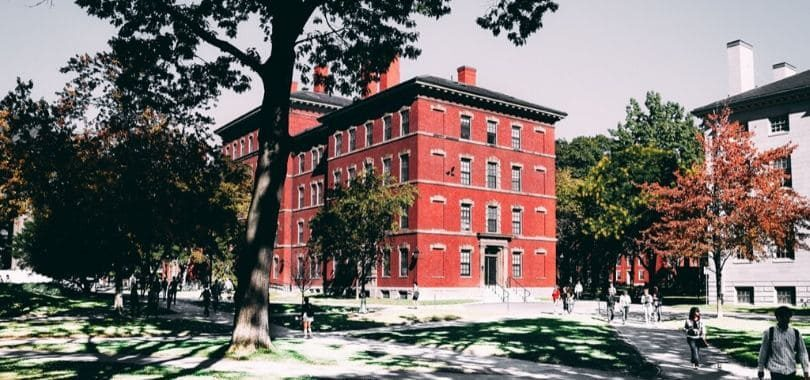 A red-bricked building on a college campus with students walking around.
