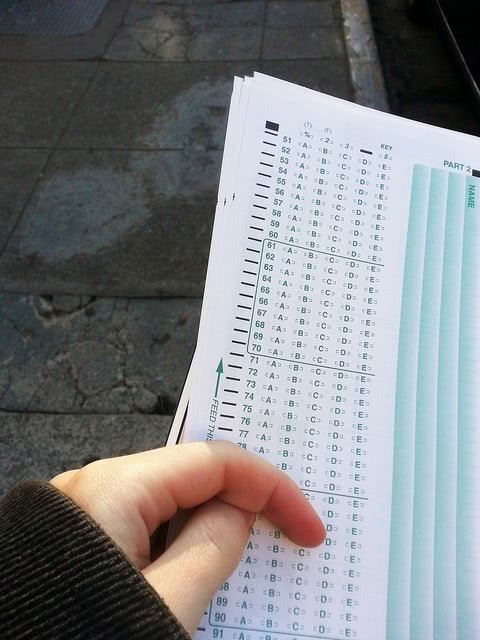 A student's hand holding a multiple choice answer sheet.