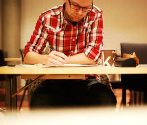 A male student wearing red checkered polo, writing on the desk.