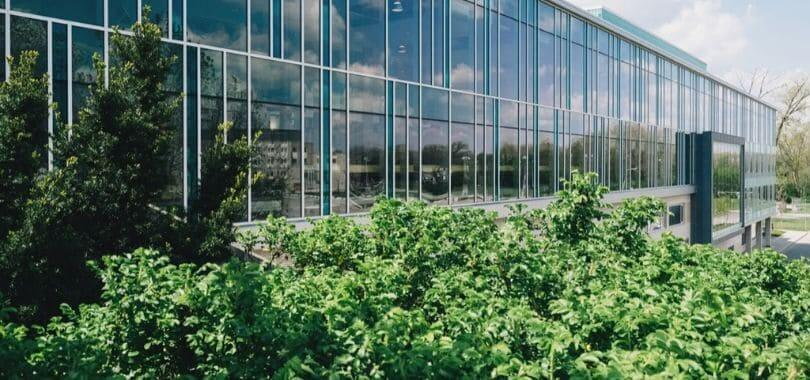 A glass building surrounded by green bushes.