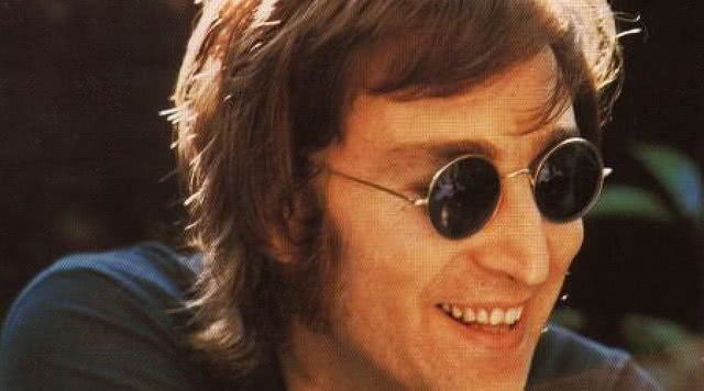 John Lennon is smiling and wearing shades.