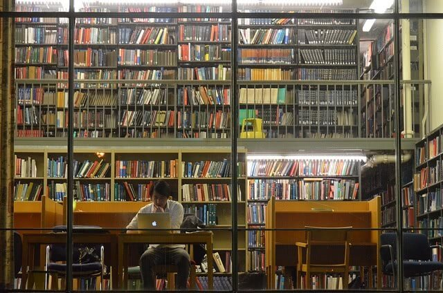 Man studying alone on his Macbook at the library showing bunch of books behind him.