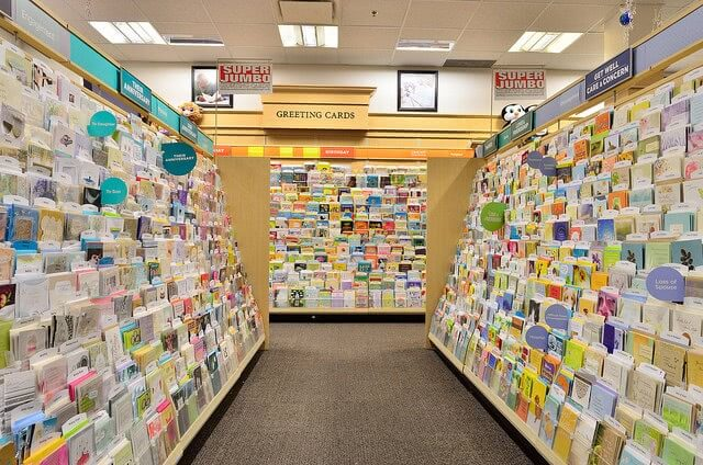 A lot of greeting cards on shelves at book store.