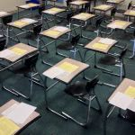 Classroom chairs with test papers on the desk.