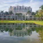 Florida International University building surrounded with coconut trees and a lake in the foreground.