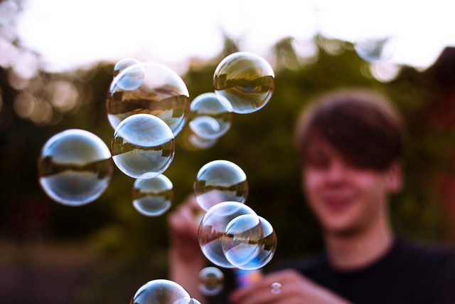 A young boy blurred in the background blowing bubbles.