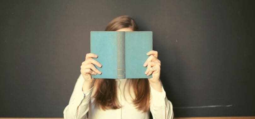 A person holding an open book in front of their face.