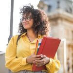 A student in a yellow jacket holding a red binder.