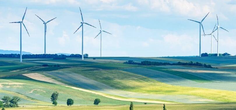 Wind turbines on grassy hills.