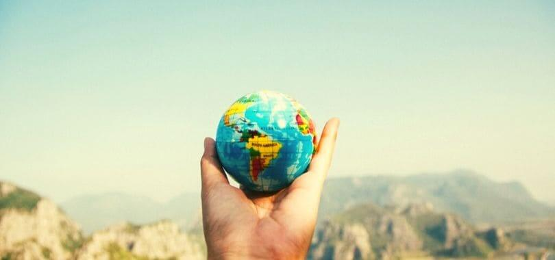 A person holding a small globe in their hand.