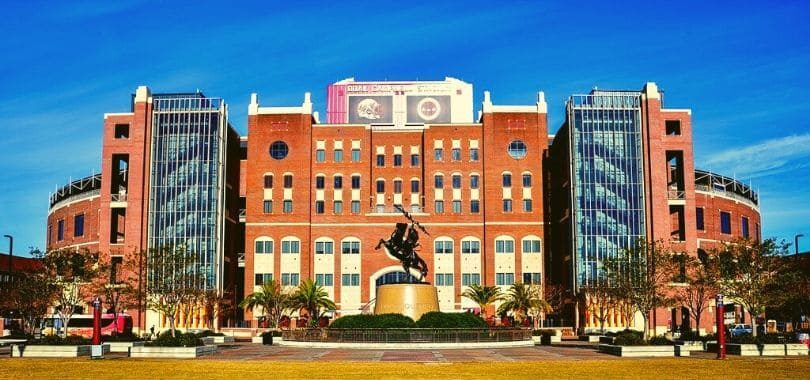 A college arena with a statue of a man on a horse in front of it.