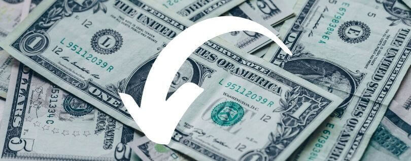 A pile of dollar bills with a white arrow pointing down superimposed on the image.