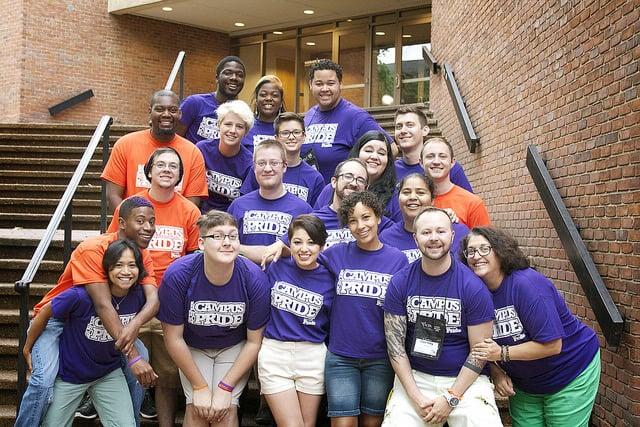"""Smiling alumni wearing violet and orange shirts that say """"Campus Pride""""."""
