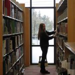 A woman standing between two shelves looking for a book.