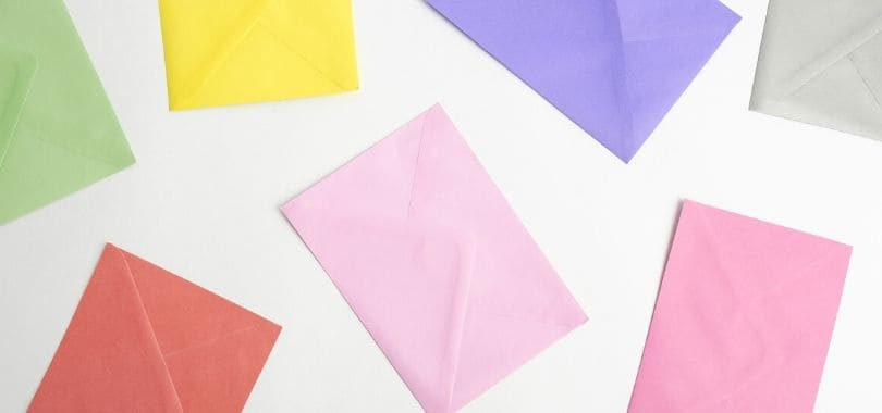 Various colorful envelopes scattered on a white surface.