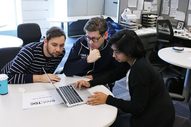 Three people having a meeting while looking at the laptop.