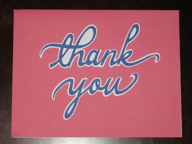 Thank you cursive font against pink background.