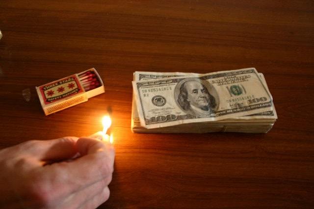A hand lighting up a match beside a pile of a dollar bill.