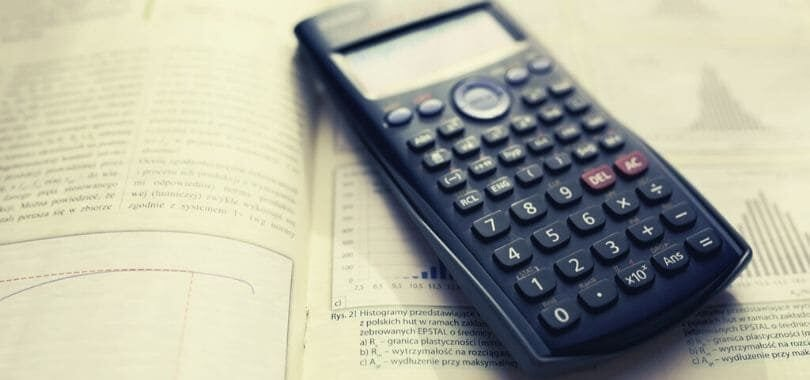 A calculator laying on top of a textbook.