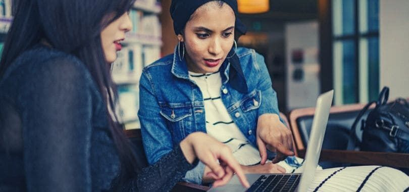 Two students sitting around a laptop applying to internships.