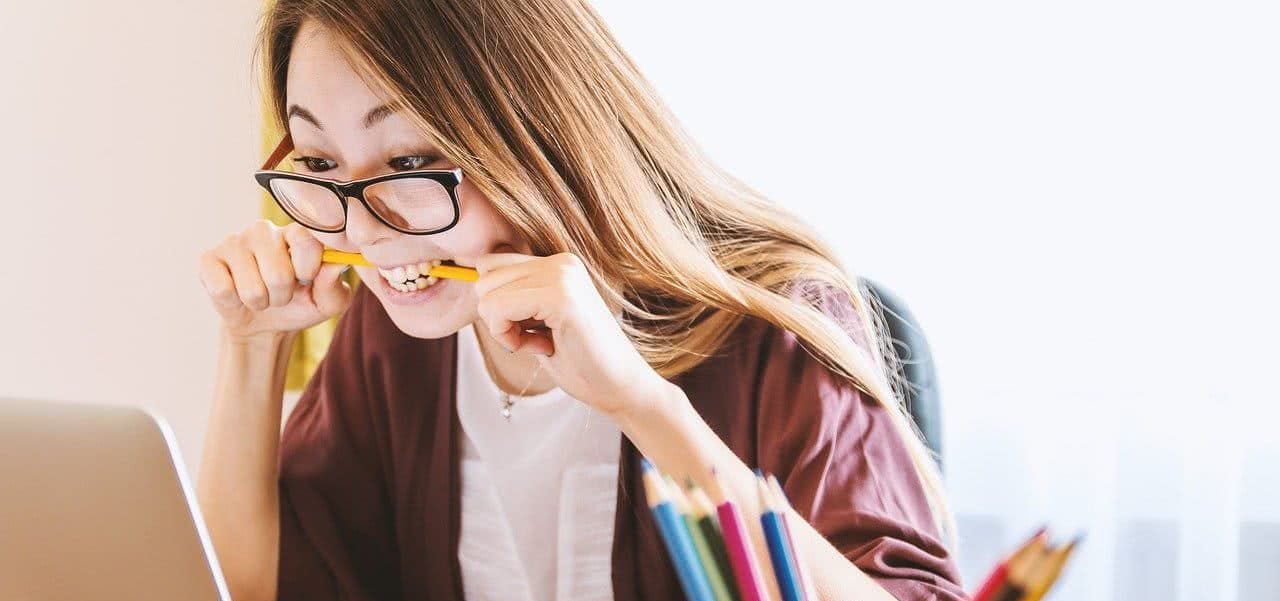 A student biting onto a pencil looking frustrated.