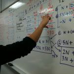 A student answers a math equation on the board.
