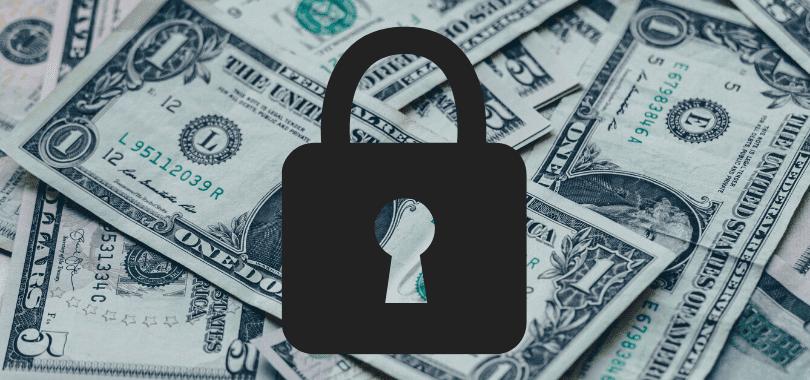 Dollar bills with a dark lock over them.