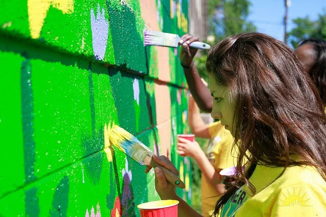 A girl is painting on the wall.