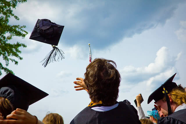 Student tossing his graduation cap in the air.