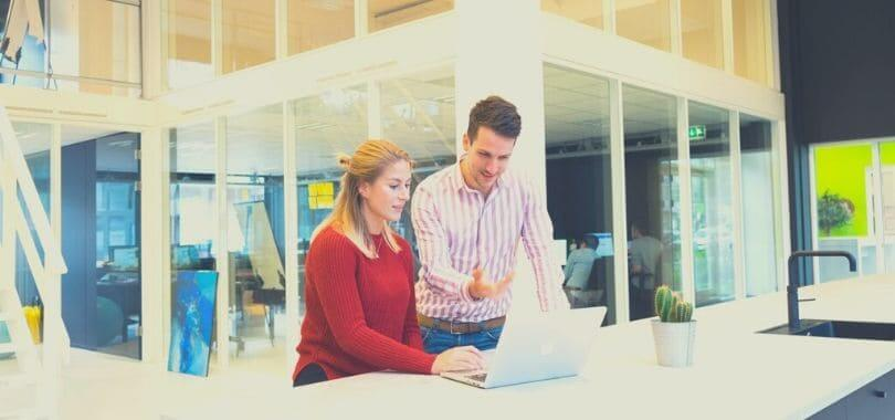 Two people standing at a desk talking while looking at a laptop.