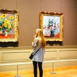 A student standing in front of multiple paintings.