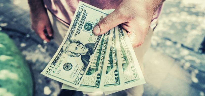 A person holding four twenty dollar bills.