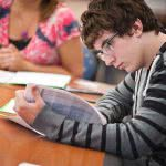 A male student is reading something on a white paper.