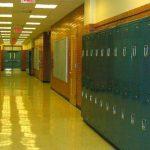 An empty high school hallway with blue lockers lining the walls.