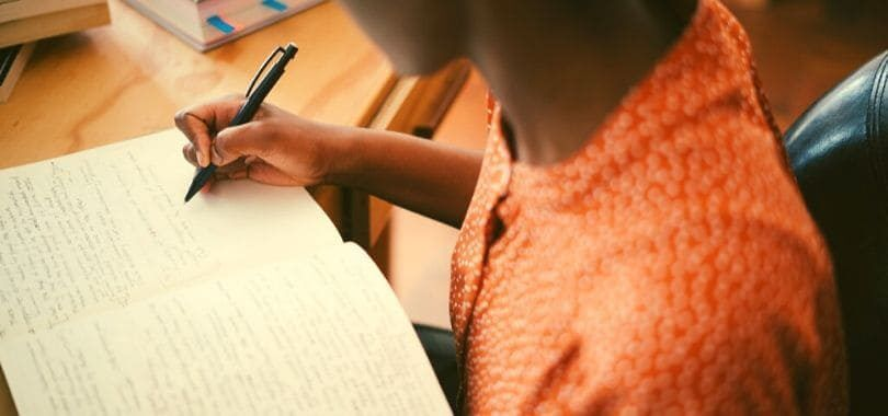 A student writing in a notebook at their desk.