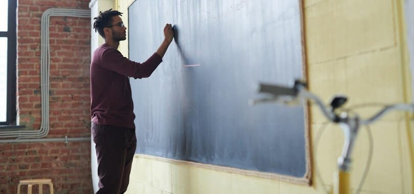 A person standing in front of a blackboard.