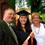 Girl on her graduation gown with her parents.