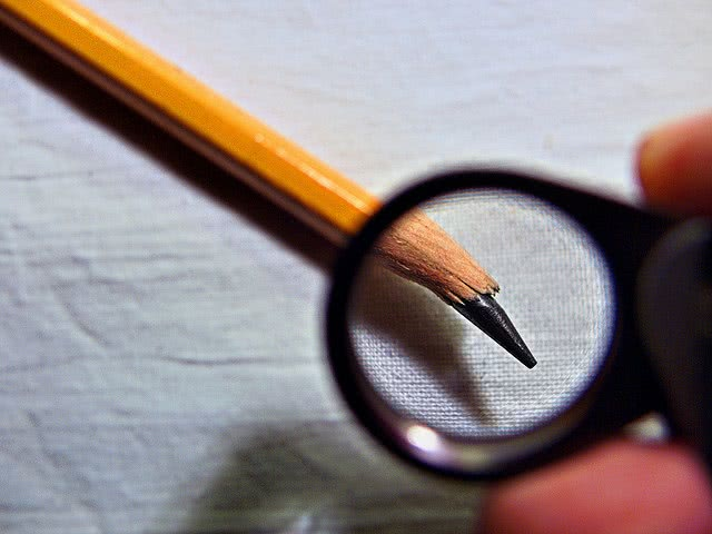 Yellow pencil with a broken tip on a blank sheet.